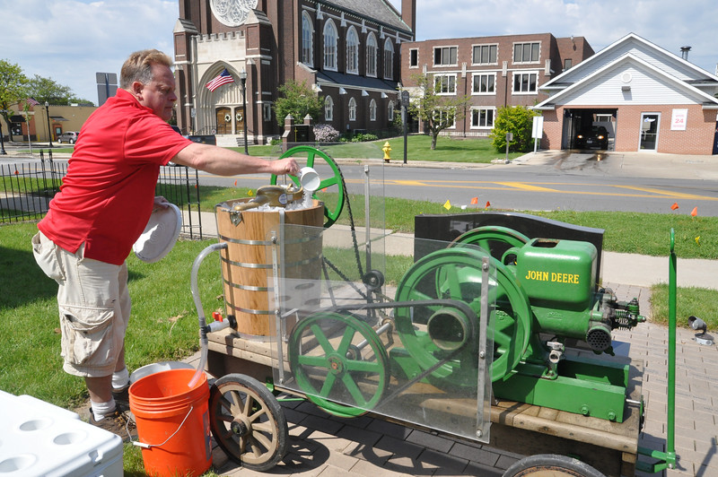 ASHLEY FOX / GAZETTE Roger Havens, president of the Wadsworth Historical Society, puts the finishing touches on homemade ice cream that he used his 1926 hit-and-miss John Deere tractor to make.