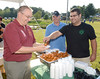 John Mainello (l) gets wings from Tim Delisle, (r) co-owner of Black Bear in Watervliet, N.Y., as Joe Skumurski looks on in middle during Wing Ding & Mac Smack Down to benefit John's son Anthony Mainello during Brunswick Farmers Market & Concert Series Tuesday, August 20, 2013 in  the town park in Town of Brunswick, N.Y.. (J.S.CARRAS/THE RECORD)