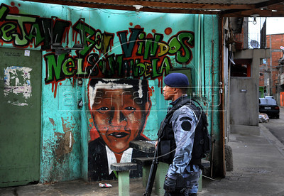 "Police officers of the Special Police Operations Battalion and Marine officers occupy to pacify the Manguinhos, Mandela, Varginha, and Jacarezinho shantytowns, Rio de Janeiro, Brazil, October 14, 2012. Graffiti in the wall says: ""Welcome to Nelson Mandela"". (Austral Foto/Renzo Gostoli)"