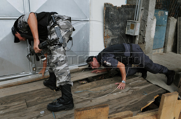 Police officers of the Special Police Operations Battalion search for drugs and guns during operation to occupy the Manguinhos, Mandela, Varginha, and Jacarezinho shantytowns, Rio de Janeiro, Brazil, October 14, 2012. (Austral Foto/Renzo Gostoli)