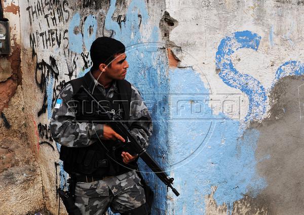 A Brazilian policeman takes position during a deployment to pacify the Manguinhos, Mandela, Varginha, and Jacarezinho shantytowns, Rio de Janeiro, Brazil, October 14, 2012. (Austral Foto/Renzo Gostoli)