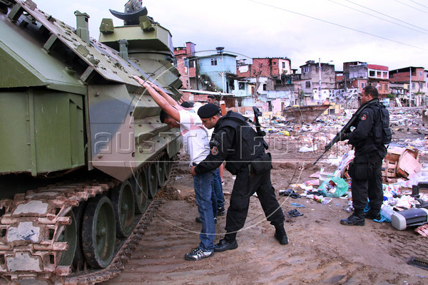 """Rio de Janeiro Special Forces Police (BOPE) search suspects with the help of Brazilian Navy armored vehicles during the """"invasion"""" of the Mandela slum in October 2012. The police/military occupation of the area was the initial stage of the implementation of a """"Pacification Police Unit"""" (UPP) in the area. Not without problems nor critics, UPPs nonetheless are credited with drastically reducing crime and securing the city in the run up to the World Cup and Olympics. (Australfoto/Douglas Engle)"""