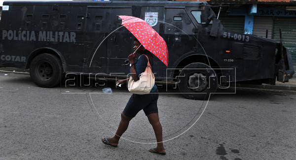 A woman past by an armoured vehicle of the Special Police Operations Battalion and Marine officers during the operation to pacify the Manguinhos, Mandela, Varginha, and Jacarezinho shantytowns, Rio de Janeiro, Brazil, October 14, 2012. (Austral Foto/Renzo Gostoli)