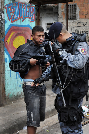 Police officers of the Special Police Operations Battalion inspects a young man during a deployment to occupy to pacify the Manguinhos, Mandela, Varginha, and Jacarezinho shantytowns, Rio de Janeiro, Brazil, October 14, 2012. (Austral Foto/Renzo Gostoli)
