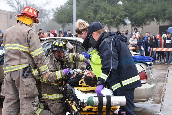 "First responders pull a student ""actor"" from a car during a reenactment at a Shattered Dreams event on Tuesday, February 11. The event took place at John Alexander Gym in Jacksonville where six school districts attended. (Jessica T. Payne/Tyler Morning Telegraph)"