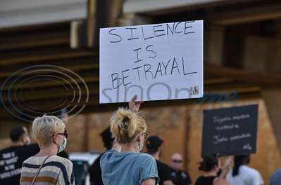 A sign of protest following the death of George Floyd is held high during a Unity Rally in downtown Jacksonville on Wednesday, June 3.