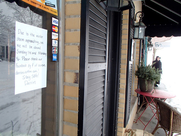 Times Sentinel photo<br /> A sign in the window of Darrin's Coffee says it all as nearly all Zionsville businesses were closed Sunday, Jan. 5, and Monday, Jan 6, due to drifting snow and frigid temperatures. Regina Owens, right, of Jewel Box Jewelers stepped outside to watch the snow.