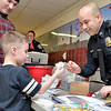Mike McMahon - The Record, L-R Devin Hayner, with dad Joh watching,  gets a badge from East Greenbush Police Sgt Ernest Tubbs, WinterFest was held at Goff Middle School, East Greenbush. Event encourages all students to become more civic-minded and involved in community events. ,  January 18, 2014.