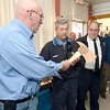 J.S.CARRAS/THE RECORD  Cohoes Fire Department Lt. Otto Madsen presents Captain Mike Spizowski an ax from the second platoon on his final day on the job after 38 years as Cohoes Chief Joseph Fahd looks on Monday, January 13, 2014 at Cohoes Central Fire Station in Cohoes, N.Y..
