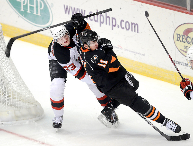 J.S.CARRAS/THE RECORD Adirondack Phantoms Kris Newbury (11) is knocked off the puck by  Albany Devils Corbin McPherson (33) during first period of AHL hockey action Saturday, January 25, 2014 at the Times Union Center in Albany, N.Y..