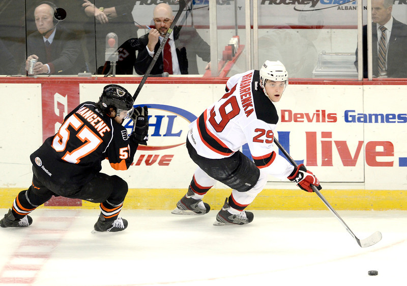 J.S.CARRAS/THE RECORD Adirondack Phantoms Matt Mangene (57) chases after Albany Devils defenseman Raman Hrabarenka (29) during first period of AHL hockey action Saturday, January 25, 2014 at the Times Union Center in Albany, N.Y..