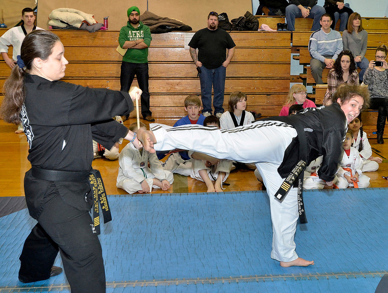 Mike McMahon - The Record, L-R Jessica Smith holds a wood board as Rachel Larsen kicks to break it, with the Columbia Tae Kwon Do demonstration. WinterFest was held at Goff Middle School, East Greenbush. Event encourages all students to become more civic-minded and involved in community events. ,  January 18, 2014.