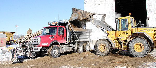 Reporter photo by Rod Rose<br /> Paul Pickett loads a sand/salt mixture into a dump truck driven by John Barrett at the Boone County Highway Department Friday morning, as crews prepared for what forecasters predicted would be a major snow storm over the weekend.