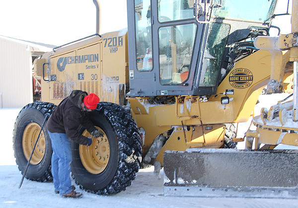 "Reporter photo by Rod Rose<br /> Nick Parr checks the tires on a Boone County Highway Department grader as the agency prepares Friday for what weather forecasters expect to be a ""significant winter storm"" over the weekend."