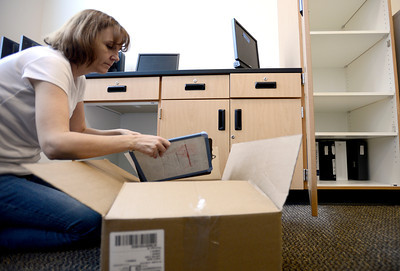0204JA2.jpg Laurie Quarnberg, special education teacher, unpacks books while getting Jefferson Academy Charter School's new building ready for classes in Broomfield, Colorado February 4, 2013.  DAILY CAMERA/ MARK LEFFINGWELL