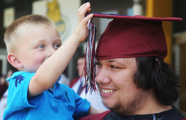 Globe/Roger Nomer<br /> Dominique Michael's step brother Hayden Lansaw, 3, plays with his tassel before Sunday's graduation.