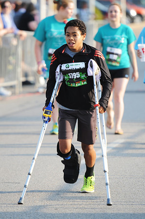 Globe/T. Rob Brown<br /> Despite a fractured ankle, Jonathan Johnson, 14, of Joplin, hobbles toward the finish line on crutches during the Memorial Run Saturday morning, May 18, 2013, in downtown Joplin.