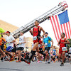 Globe/T. Rob Brown<br /> Runners start the Memorial Run under the Joplin Fire Department Ladder Truck No. 1 and the US flag Saturday morning, May 18, 2013, in downtown Joplin.