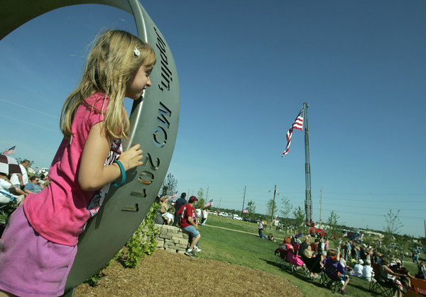 Globe/Roger Nomer<br /> Kaycee O'Dell, 6, watches the ceremony at Cunningham Park from her perch on the memorial ring on Tuesday afternoon.