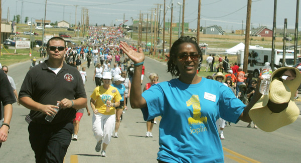 Globe/Roger Nomer<br /> Melodee Colbert-Kean waves to watchers along the route on 20th Street during Tuesday's Walk of Unity.