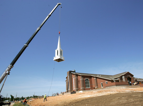 Globe/Roger Nomer<br /> The steeple for the LDS Stake Center is lowered into place at a stop along the Walk of Unity on Tuesday.