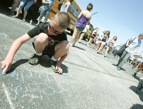 Globe/Roger Nomer<br /> Luke Linscheid, 8, chalks a message for walkers along the Walk of Unity route at Joplin High School on Tuesday.