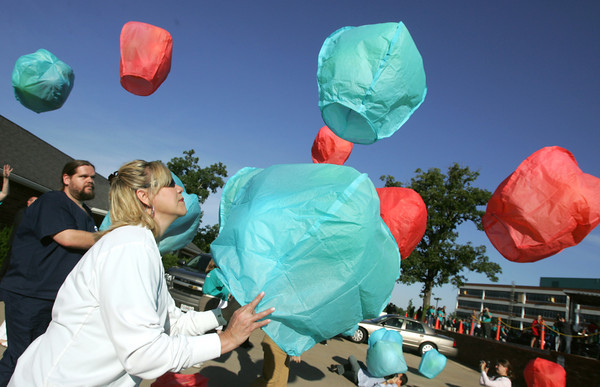 Globe/Roger Nomer<br /> Renee Denton, director for medical oncology and pediatrics at Freeman, releases a latern during Tuesday's Morning Has Broken event at Freeman Hospital.  The laterns were in rememberance of the tornado victims.