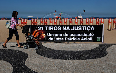 "A woman with a baby past by twenty one images of bullets were set up in Copacabana beach by non governmental organization Rio of Peace (Rio de Paz) on the anniversary of the murder of Brazilian judge Patricia Acioli -shot dead as she returned home-, Rio de Janeiro, Brazil, August 10, 2012.In the banner says: ""Twenty bullets into Justice"".  Brazilian judge Patrícia Acioli was killed on August 11, 2011 by two gunmen apparently under orders of policemen involved in private security militia. (Austral Foto/Renzo Gostoli)"