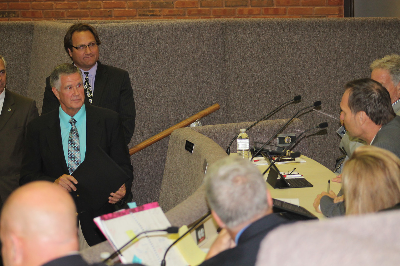 LAWRENCE PANTAGES / GAZETTE Retiring Medina City Schools Superintendent Dave Knight (left, foreground) listens as Councilman Jim Shields (right) thanks him for his service to the district during Medina City Council's Monday night meeting. Knight was honored with a resolution in a surprise presentation.