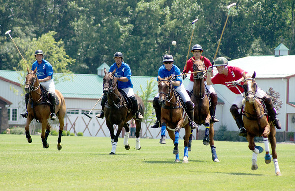 Greg Chandler, far right, leans in to strike the ball during the Key Bank polo team's competition against the Lexington Polo Club Saturday, July 13, at the Wells Fargo Polo Field, Whitestown. Austin Chandler backs up his dad against the Lexington challengers, who are in blue, at the 10th Annual Boone County Polo Charity Event. Proceeds from the charity benefit the Witham Health Services Foundation and Boone County Senior Services.