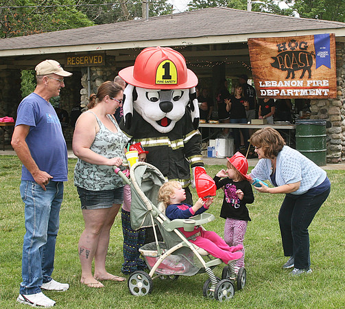 Rod Rose The Lebanon Reporter<br /> HOG ROAST HANDOUT: Sparky the Fire Dog, the Lebanon Fire Department mascot, greets (from left) David Long, Morgan Long, Cynthiana LOng, December Long (behind stroller) and Caren Archer, who adjusts one of the sourvenir fire helmets Sparky gave to children at the dinner Saturday in Lebanon's Memorial Park.