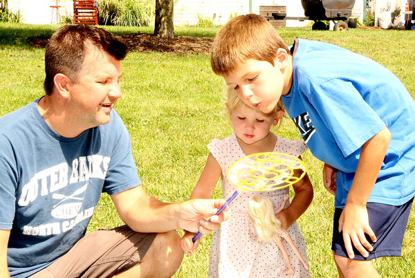 Family Time: Josh Weirich (left) helps his daughter Cassie, 1, with the bubble wand while her brother Brandt, 7, tries to blow bubbles during Tuesday's Family Day at the Boone County 4-H Fair.
