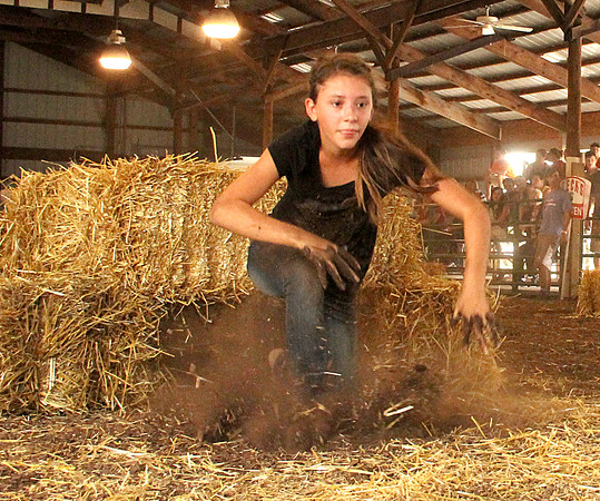 Up And Out: Llama Barn member Autumn Ryan eyes her watermelon as she makes the turn during the Battle of the Barns competition Thursday at the Boone County 4-H Fair.