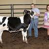 Rod Rose The Lebanon Reporter<br /> FEEDER CALF GRAND CHAMPION: Ellie Garst, joined by Boone County Fair Queen second runner-up Emma Mendez, receives the trophy for exhibitin the grand champion feeder calf, Saturday at the Boone County 4-H Fair.