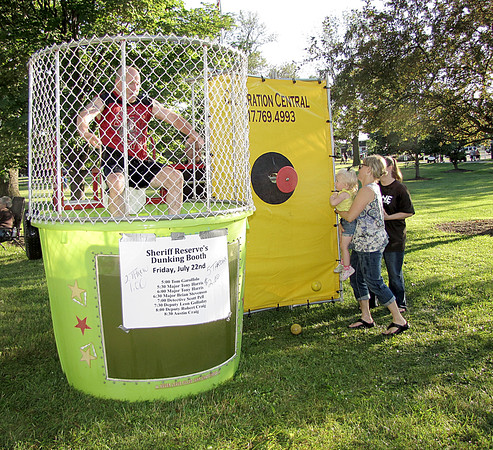 Rod Rose The Lebanon Reporter<br /> INTO THE DRINK: Hayley Trojnar, 2-1/2, held by grandmother Cathy Adams, sends Boone County Sheriff's Deputy Leon Gollowday into the dunk tank Friday evening at the Boone County 4-H Fair. It was refreshing, Gollowday said.