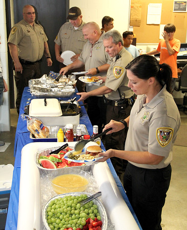 "Thoughtful Gesture: Boone County Sheriff's Office workers (from bottom) Annie Greene, Joe Rady, Robert Hatfield, Joe Grzybowski, and Jermy Smith que up to go through the buffet line set up in the bottom of the Boone County Jail Thursday afternoon. Lebanon First Baptist Church and the Laughter and Love Daycare put on the affair for Boone County Sheriff employees and the Lebanon Police Department. LFBC men's fellowship member Ron Forsythe said the groups wanted ""to show our love and support for our officers."" Pulled pork and pork burgers were supplied by the Boone County Pork Producers, and other items included green beans, macaroni and cheese, fresh fruit and a dessert table. Sheriff's dispatcher Sara Forsythe, and daughter of Ron, said the daycare also provided handmade pictures of childeren's hands and feet with the ""Blue Line"" through the middle for most officers to show their appreciation."