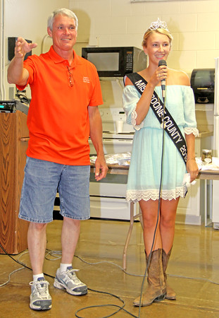 Crucial Negotiation: Volunteer auctioneer Tom Dull stands with Boone County 4-H Fair Queen Gabi Reese as she trys her hand at being an auctioneer during the sale of the traditional queen's cake.