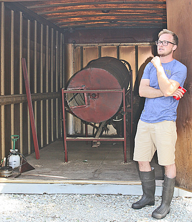 SMOKIN' HOT: Caleb Michalke, co-owner of Sugar Creek Malt. Co., describes the process though which malt grains are smoked. The smoker can handle 400 pounds of grains at once and churns constantly as the room fills with apple wood, lavender or tequila barrel smoke.