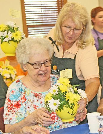 "BLOOMING SMILES: <br /> Elizabeth Pearl| The Lebanon Reporter<br /> DAISY DAY: Mount's Flowers and Gifts owner Lana Hale (right) hands a mug of yellow and white daisies to Lebanon resident Mary Allen on Wednesday at Boone County Senior Services Inc. Hale, along with several 4-H and FFA members, surprised the lunch crowd with the bright bouquets.<br /> ""I don't have words to say,"" Allen said. ""It made me smile. If it doesn't make someone smile they're beyond help. They're fantastic.""<br /> The mugs were donated by Teleflora, a national flower delivery company, as part of their ""Make Someone Smile Week."" This was the first year that Mount's has been able to participate, with flowers donated by three of the company's wholesalers, Hale said. On Tuesday, the company delivered bouquets to Homewood Health and Hickory Creek. Hale, along with her student volunteers, put together about 96 bouqets total, she said. On Wednesday they planned to take extras to the Lebanon Police Department and the Boone County Sheriff's Office. <br /> The flowers lit up a lot of the lunch-goers faces on Wednesday, said BCSSI executive director Anita Bowen. <br /> ""I've seen a lot of smiles around the room,"" Bowen said. ""It seems amazing."""