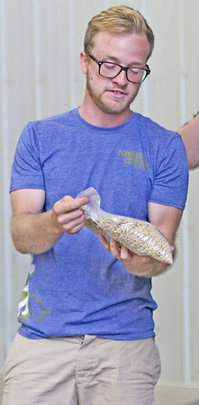 GRAIN ON THE BRAIN: Caleb Michalke, co-owner of Sugar Creek Malt Co., shows off a bag of malted grain.