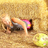 Squeezing Through: Hores Barn team member Paige Armstrong slides through hay bales en route to picking up her greased watermelon during Thursday's Battle of the Barns at the Boone County 4-H Fair.