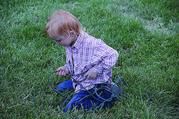 Maggie Morris, 3, of Cicero, practices the skills needed to rope a calf as her parents Amy and David Morris watch the Indiana High School Rodeo Association's calf roping contest at the Rodeo Bash at the Boone County 4-H Fairgrounds Saturday night.
