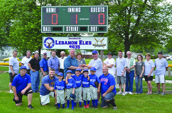 "Lebanon Elks Lodge president Walter Burtner presents Scott Hood, president of the Lebanon Little League, with the scoreboard remote at Wednesday's scoreboard dedication. The Elks lodge raised $5,000 for the scoreboard and sign in 30 days. Lebanon Little League sponsorship and fundraiser chair, Dianna Kincaid said, ""because of their generosity, every baseball and softball field at Lebanon Little League now has a scoreboard."""