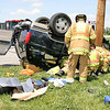 Whitestown Fire Department firefighters remove one victim of a two-vehicle accident in which one person died and another suffered critical injuries Thursday afternoon at Indiana 267 and Indianapolis Road.