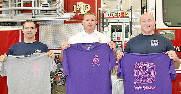 Rod Rose The Lebanon Reporter<br /> For the fourth year, the Leanon Fire Department will be selling T-shirts, with proceeds benefiting the Boone County Cancer Society, at tonight's barbecue dinner at Lebanon's Memorial Park, and at the Battle of The Barbecue later this year. Holding sample shirts are (from left) Lt. Luke McQueen; Chief Chuck Batts and Probationary Firefighter Jason Fussell. The shirts are $11. They will also be available at LFD's Station 11, 975 Lasley Drive, during regular business hours.
