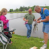 Rod Rose The Lebanon Reporter<br /> FISHING DERBY FIND: Mariah Curet, 7, and her dad, Joe Curet, wait as Lebanon Kiwanis member Jason Marshall measures the 21-inch catfish Mariah caught at Saturday's fishing tournament.