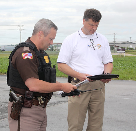Rod Rose The Lebanon Reporter<br /> REVIEWING INFORMATION: Boone County Sheriff Major Tony Harris and Det. John Ford inspect photo IDs being distributed to officers at the scene of a stabbing Wednesday at the Kentucky Fried Chicken restaurant on state Route 32 in Lebanon.