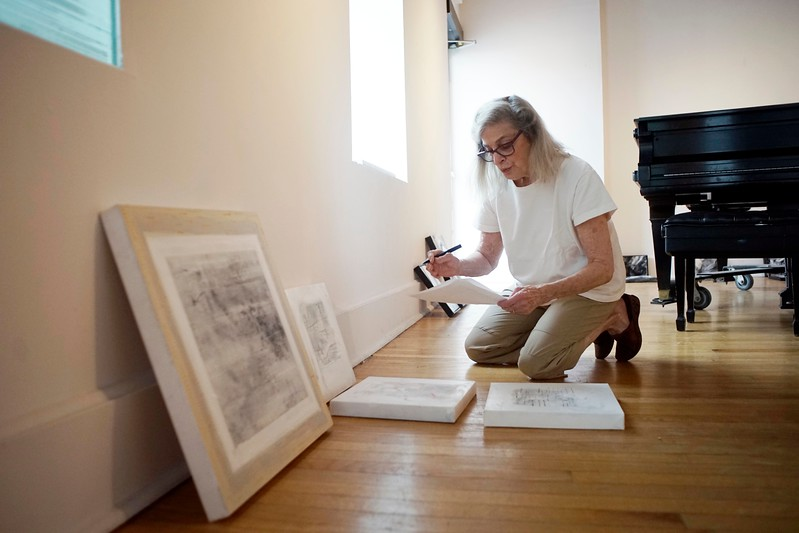 BEN GARVER — THE BERKSHIRE EAGLE<br /> Artist Karen Chase prepares her exhibit abstract paintings in Lichtenstein Center for the Arts to open Friday August 4. The Lenox artist and poet is hanging about 80 of her works. Chase avoids painting anything representational, exploring paint and motion, separate from the world.