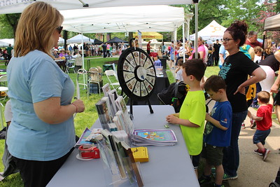 Medina County Health Department's Christy Rickbrodt asks basic safety questions Saturday to Trey, Lincoln and Audra Spring as the children attend the annual Kids Day of Safety and Play on Public Square in Medina. LYDIA MAINZER / GAZETTE