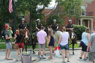 Medina County Sheriff's Department's Mounted Auxiliary Unit hands out stickers Saturday during the annual Kids Day of Safety an Play on Public Square in Medina. LYDIA MAINZER / GAZETTE